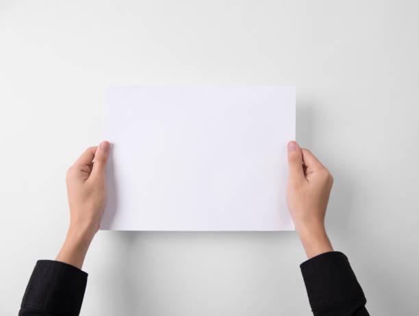 die Hand zeigt leeres Papier A4-Flyer zum Mockup Vorlage Logo-branding auf grauem Hintergrund. – Foto