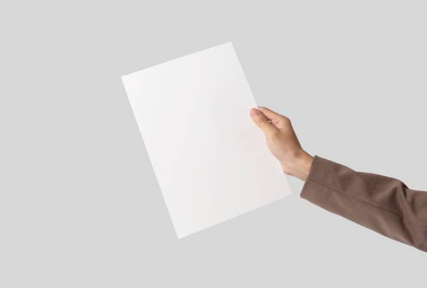 Hand zeigt leeres Papier A4 Flyer für Mockup-Schablone Logo-Branding auf grauem Hintergrund. – Foto
