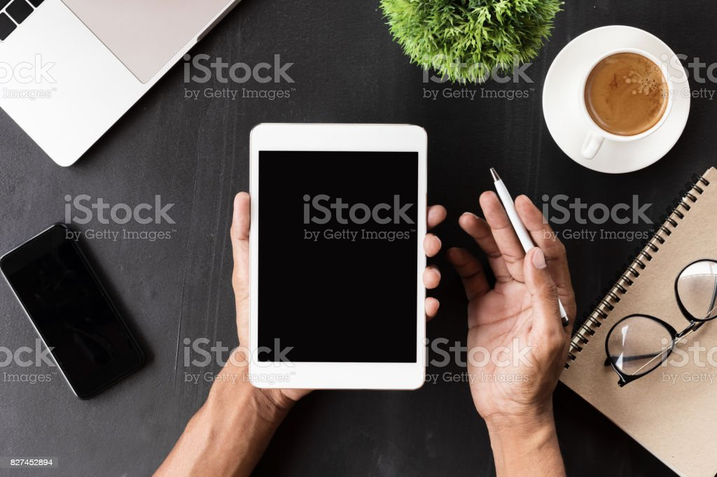 hand showing digital tablet blank screen on work desk stock photo