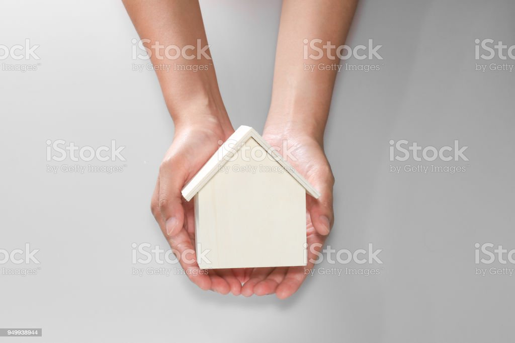 hand showing little wooden house stock photo