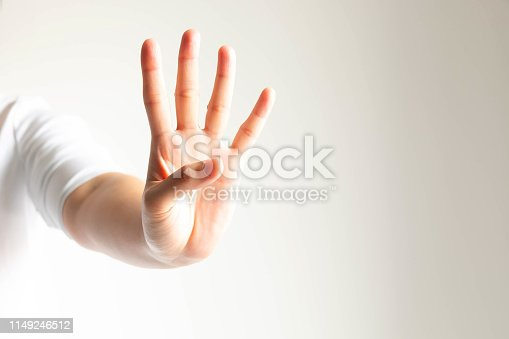 Woman in white T-shirt stretch out her hand forward and raising fingers exceprt thumb for meaning the fourth; or counting number four.