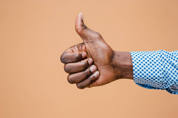 hand showing ok sign isolated on brown background - thumbs up стоковые фото и изображения
