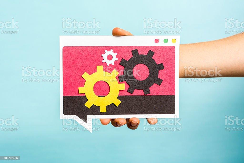 Hand showing three gears interlocked on speech bubble, blue background stock photo
