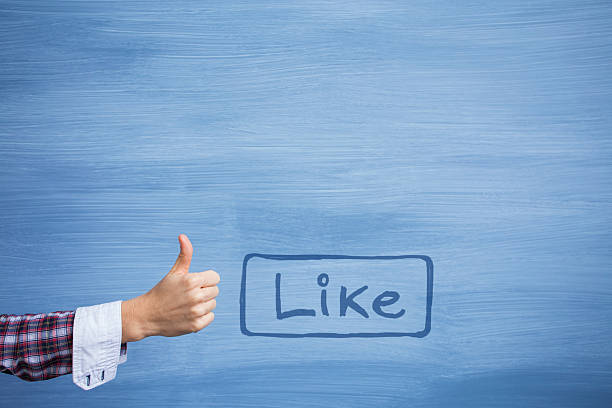 Hand showing thumbs up gesture and like button stock photo