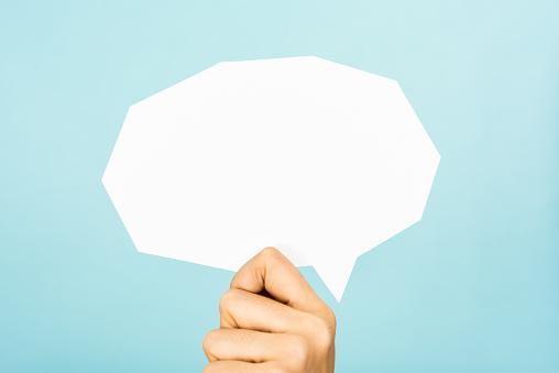 istock Hand showing white blank speech bubble, straight cutting, blue background. 465462550