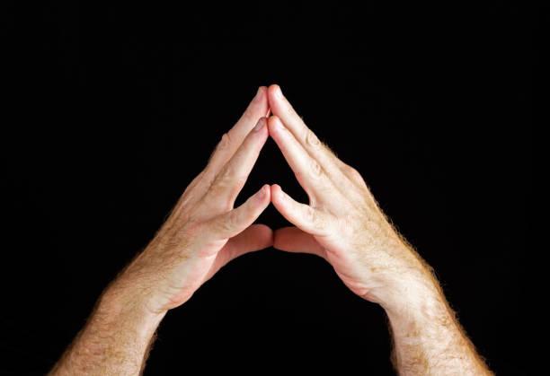 zeichen der hand: zwei männliche hände faltete in gedanken auf schwarz - kirchturmspitze stock-fotos und bilder