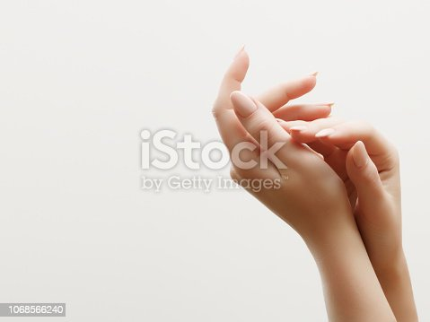 Hand skin care. Closeup of beautiful woman hands with light manicure on nails . Cream for hands and treatment.