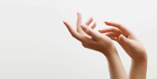 손 피부 관리입니다. 손톱에 빛 매니큐어와 아름 다운 여자의의 근접 촬영 크림 손 및 치료에 대 한입니다. - 매니큐어 화장품 뉴스 사진 이미지