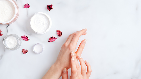 1151624350 istock photo Hand skin care concept. Top view female hands applying organic moisturizing hand cream, jars with cosmetic cream and pink petal on marble table. Natural organic beauty products 1199860643