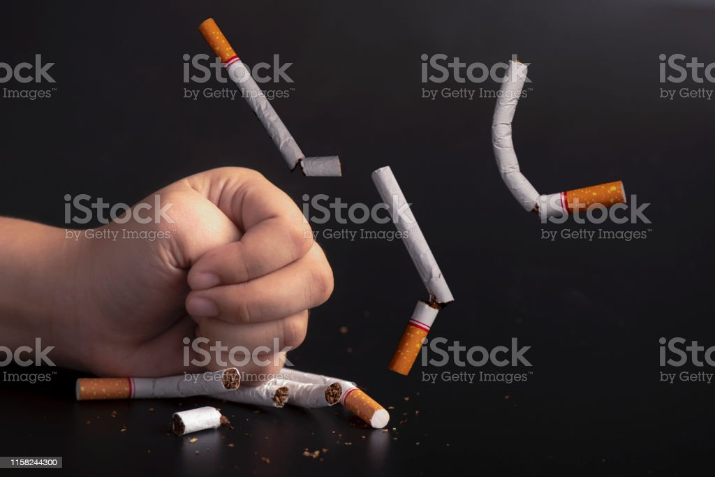Hand smashed cigarettes stop smoking concept