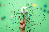 Hand spinning paper soccer ball on green background. Origami. Paper craft. Soccer game concept.