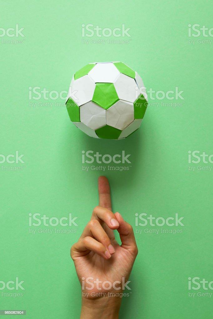 Balón De Fútbol De Papel Mano Spinning Sobre Fondo Verde Origami