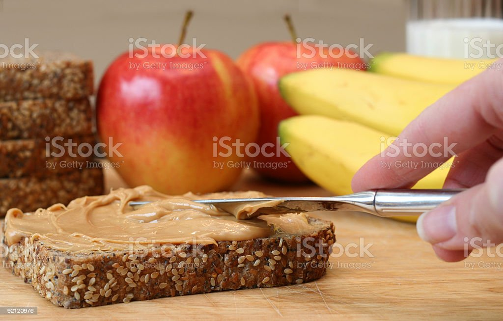 Hand spreading peanut butter on wheat bread with knife stock photo