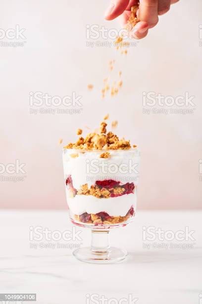 Hand sprinkling granola over healthy raspberry yogurt parfait in a picture id1049904106?b=1&k=6&m=1049904106&s=612x612&h=6 nzhqav161bcujfgvhyhw00ifhgwsh4pxkbial k8i=