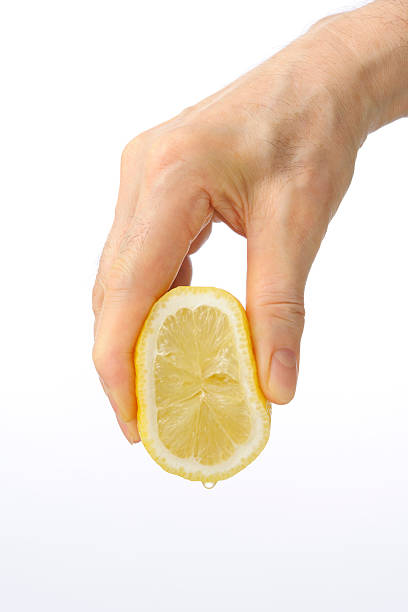 Hand squeezing a lemon against on white background Close-up of hand squeezing a lemon isolated on white background. lemon juice stock pictures, royalty-free photos & images