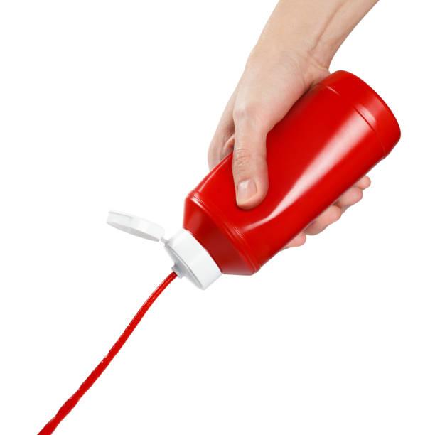 mão espremendo ketchup de uma garrafa de plástico em branco - squeeze bottle - fotografias e filmes do acervo