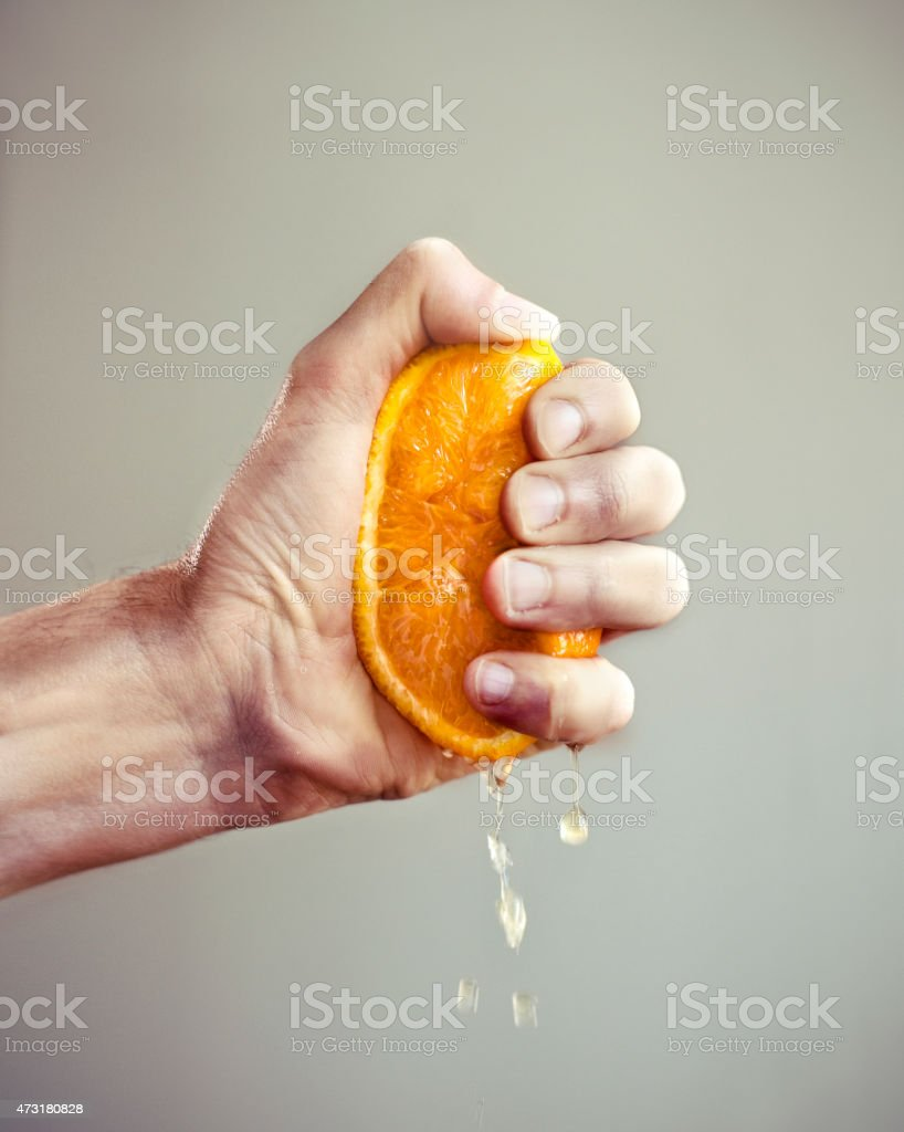 Hand squeezing orange stock photo