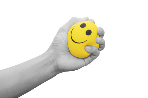 Hand squeezing smiling face yellow stress ball, isolated on white background stock photo