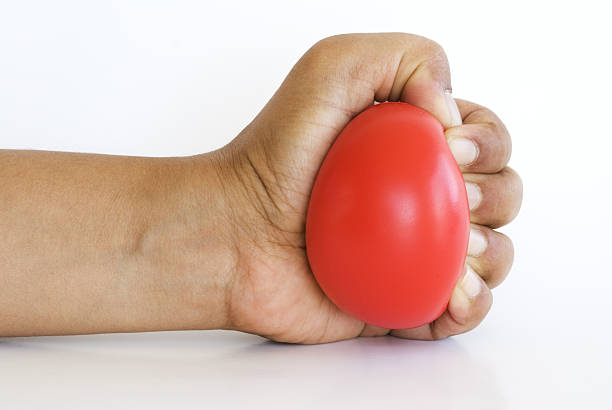 hand squeezing stress ball - squeezing stock pictures, royalty-free photos & images