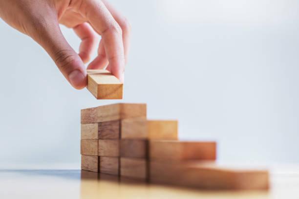 mano pila maderas paso de bloque en la tabla. concepto de desarrollo de negocio - foto de stock