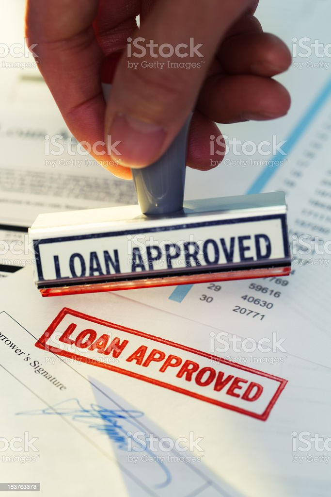 """Hand Stamping """"Loan Approved"""" with Rubber Stamp on Banking Paperwork stock photo"""
