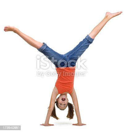 A young girl doing a handstand on a white background.