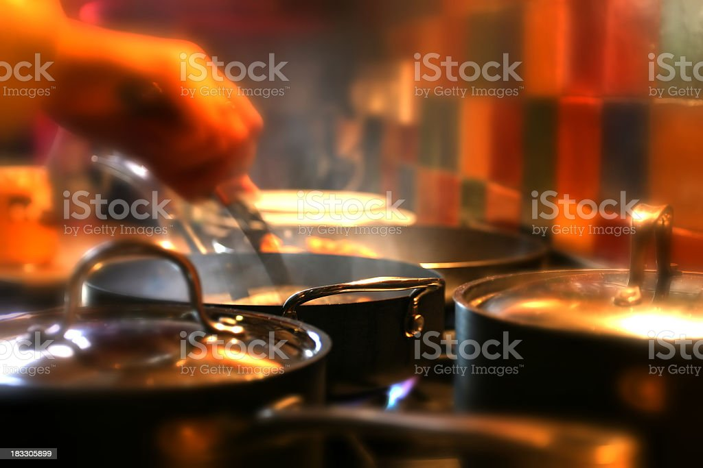 Hand stirring food in pan surrounded by other pots and pans royalty-free stock photo