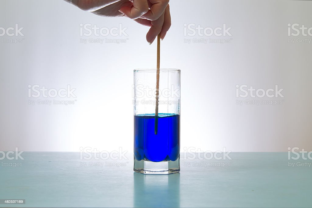 hand stirs  blue liquid in  glass with stick stock photo