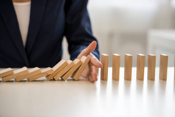Hand stopping falling blocks on table stock photo