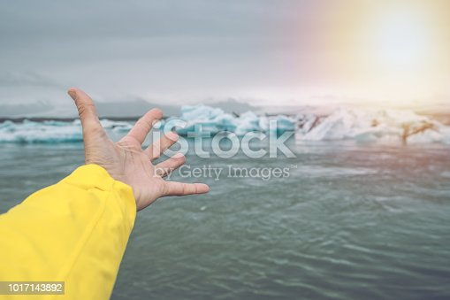 Hand stretches towards glacier lagoon icebergs  People nature concept. Shot in Iceland, Europe