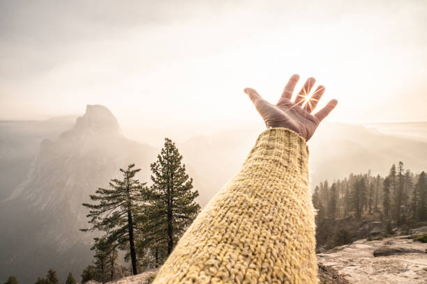 Hand stretches towards sunrise on top of Yosemite valley , USA stock photo