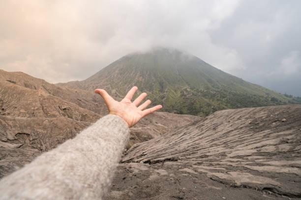 Hand erstreckt sich in Richtung Vulkankrater – Foto