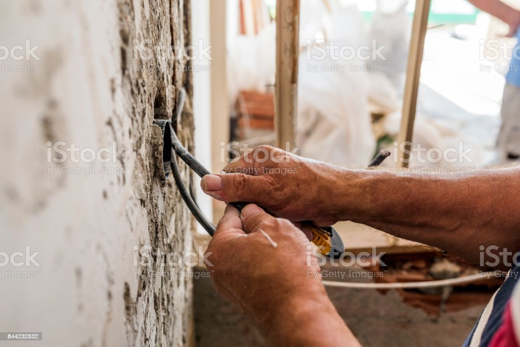 Hand striping the insulation of wires stock photo