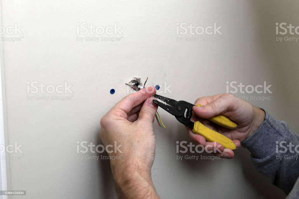 Hand stripping wires for thermostat control for HVAC system stock photo