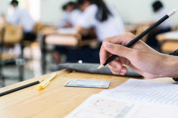 hand student testing in exercise taking fill in exam carbon paper answer sheet with pencil at school or university in test room, document exams at campus classroom, education or back to school concept stock photo