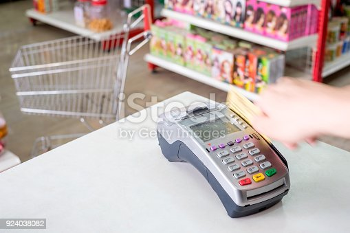 914593772istockphoto Hand swiping credit card on payment terminal in store 924038082
