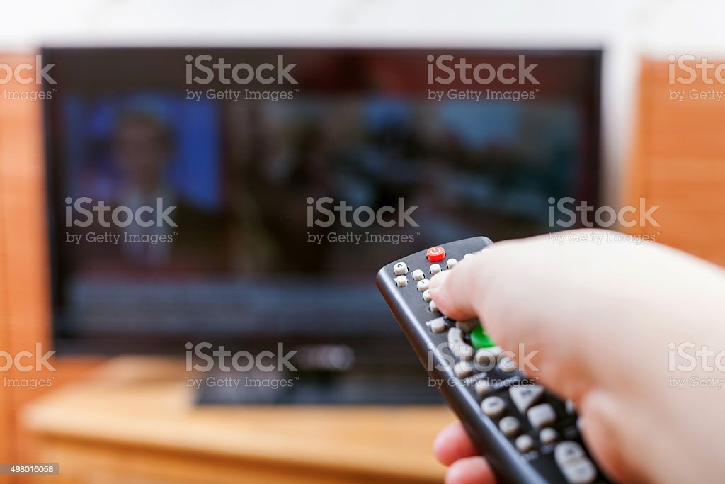 Hand switches TV channels with news stock photo