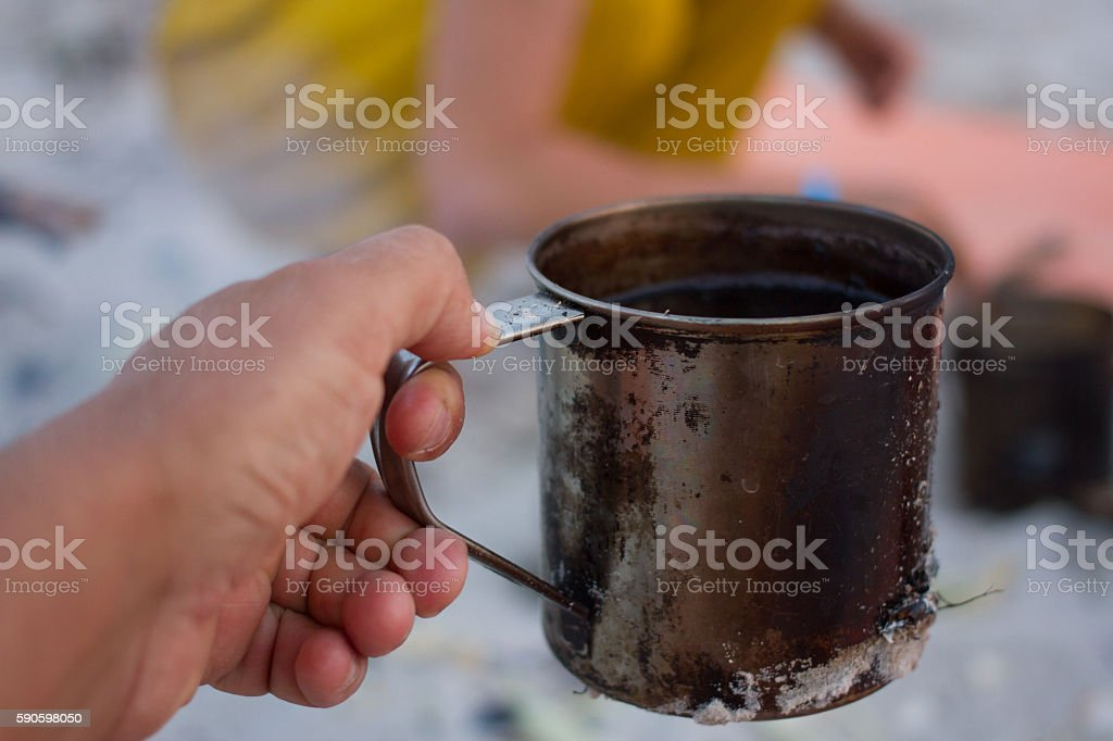 Hand take metal cup for heating. Tourism, travel, morning cooking stock photo