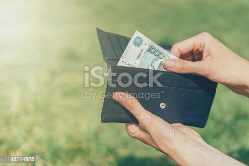 Close-up hands takes out a banknote of Russian rubles from a wallet on green background outside