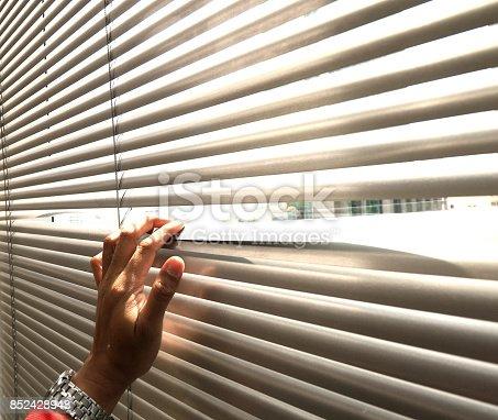 istock Hand taking a peek through the window blinds 852428948