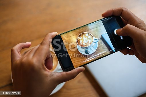 Hand taking a picture of hot latte art coffee cup with art foam on wooden table with her smart phone sitting at a coffee shop snap and share on social media by smartphone. Web Blogger photo shoot concept.