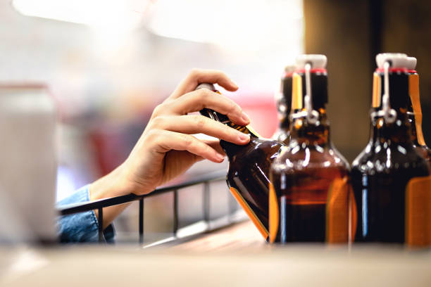 hand taking bottle of beer from shelf in alcohol and liquor store. customer buying cider or supermarket staff filling and stocking shelves. retail worker working. - alcool imagens e fotografias de stock