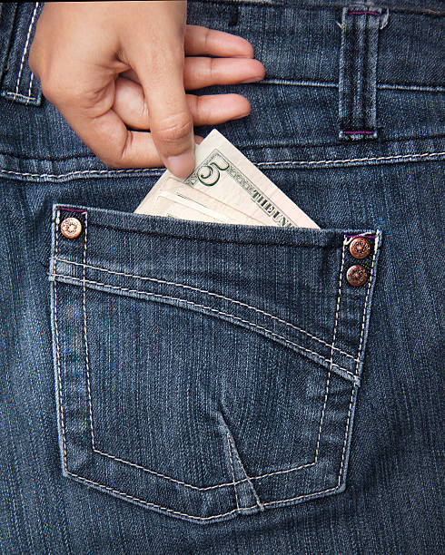Hand taking money from pocket stock photo
