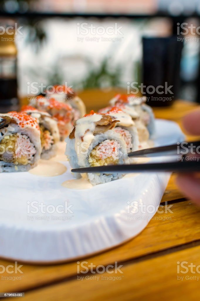 Hand taking sushi roll with chopsticks stock photo