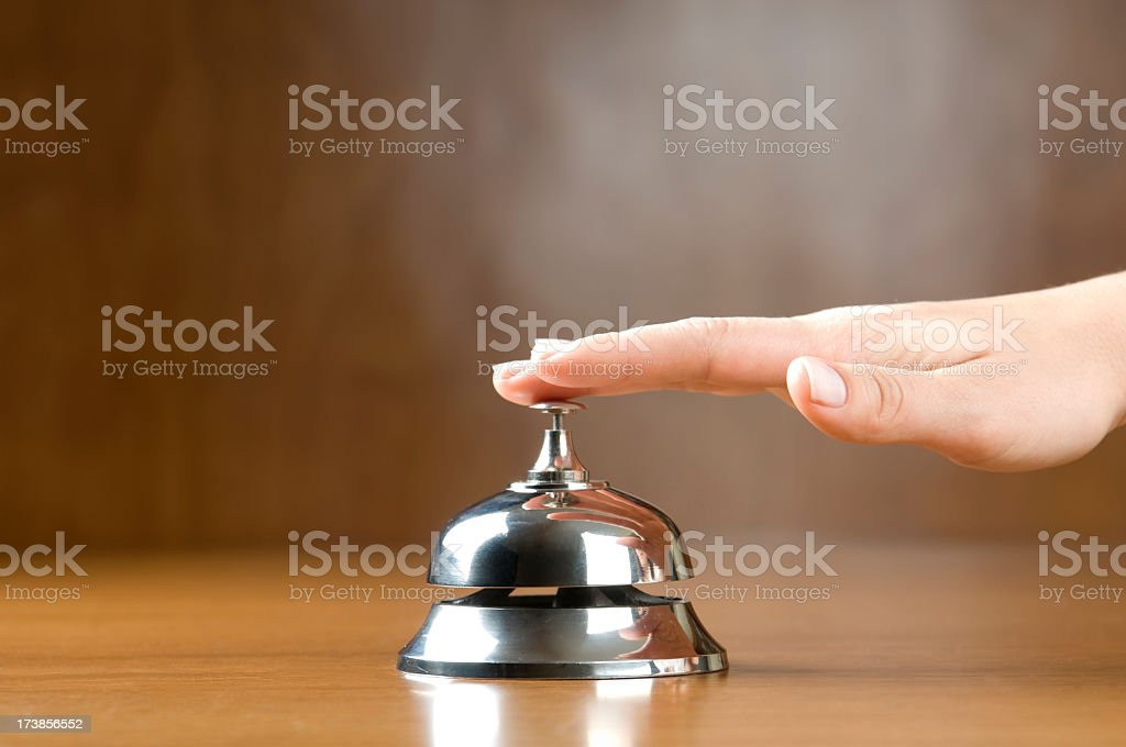 A hand tapping a service bell on a desk woman ringing service bell (selective focus on finger) A Helping Hand Stock Photo