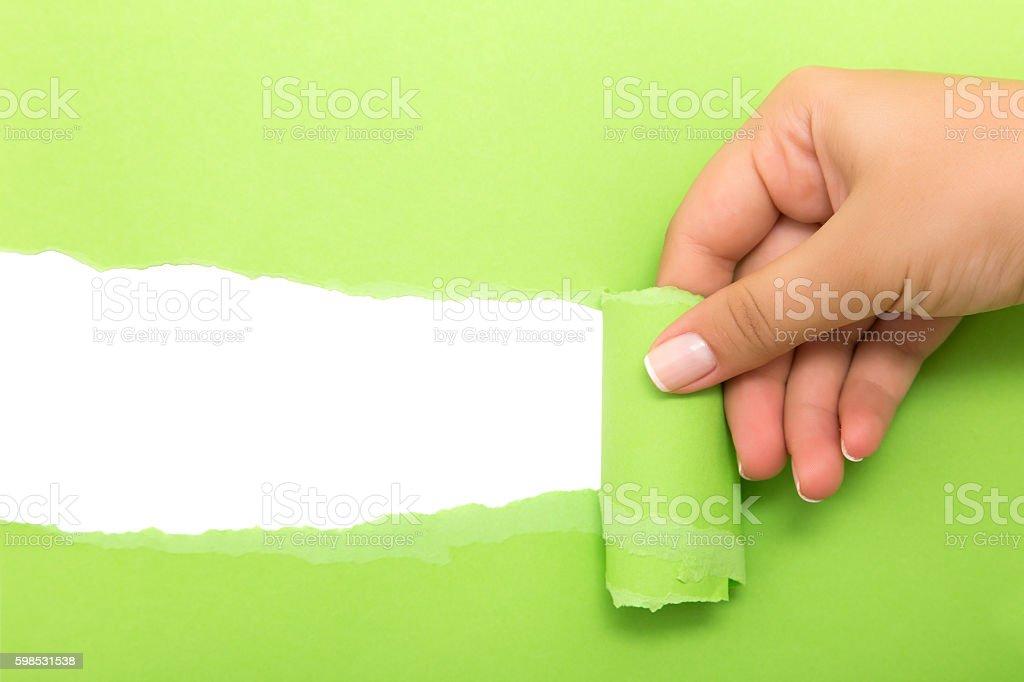 Hand tear a strip of green paper photo libre de droits