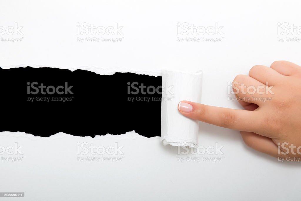 Hand tear a strip of white paper photo libre de droits