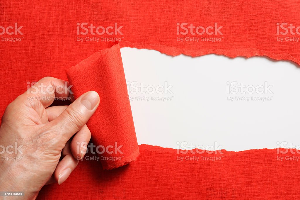 Hand tearing a red paper against white background stock photo