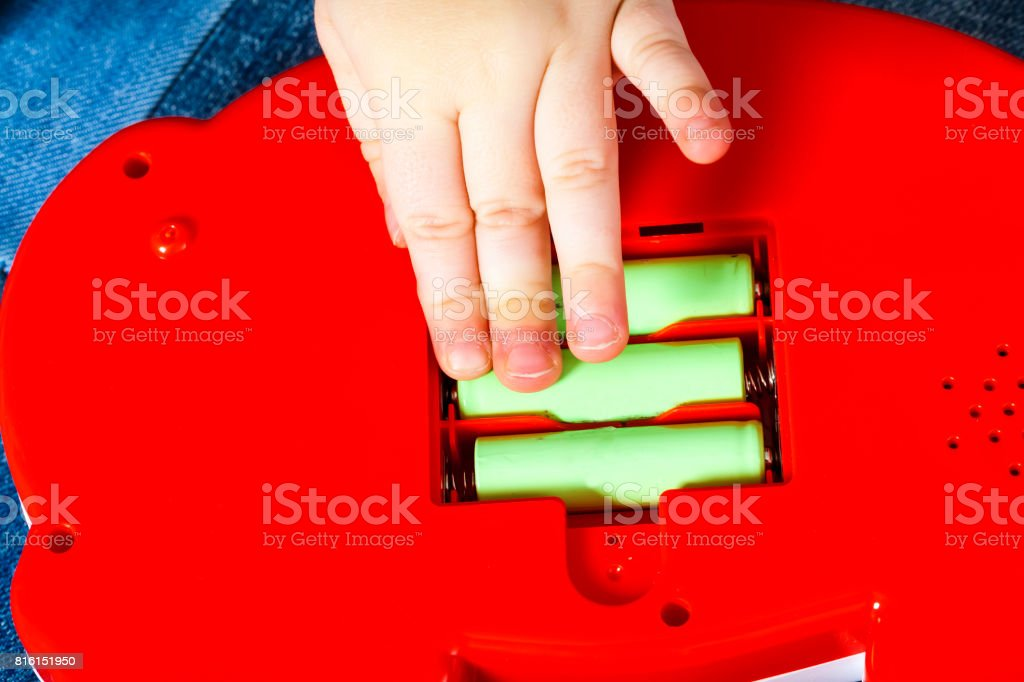 hand the child put the batteries in the toy stock photo