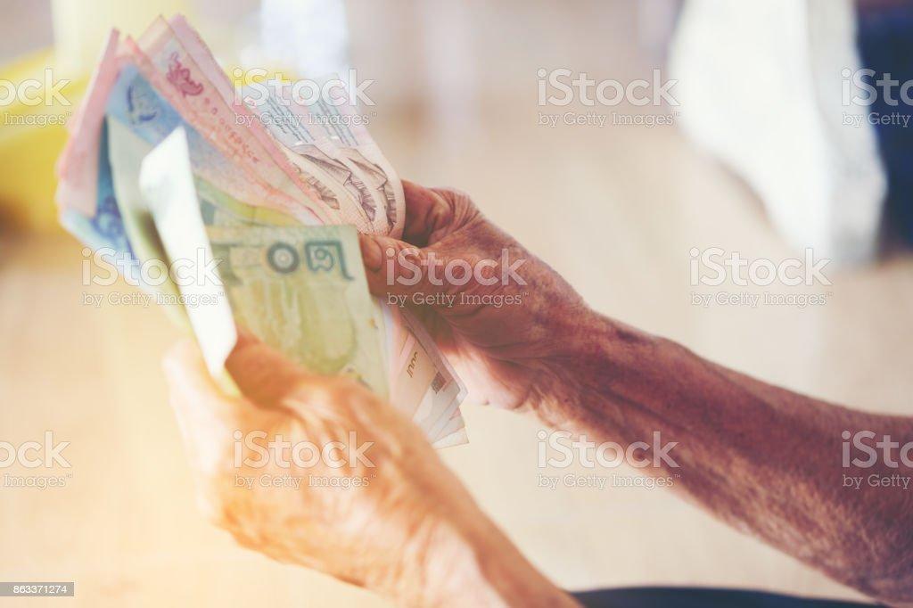Hand der alte Mann die Banknote thai Geld zum sparen. Geld sparen-Konzept, nutzen ältere Menschen, Graubart halten und Geld in der hand, zeigt lokale Thailand – Foto